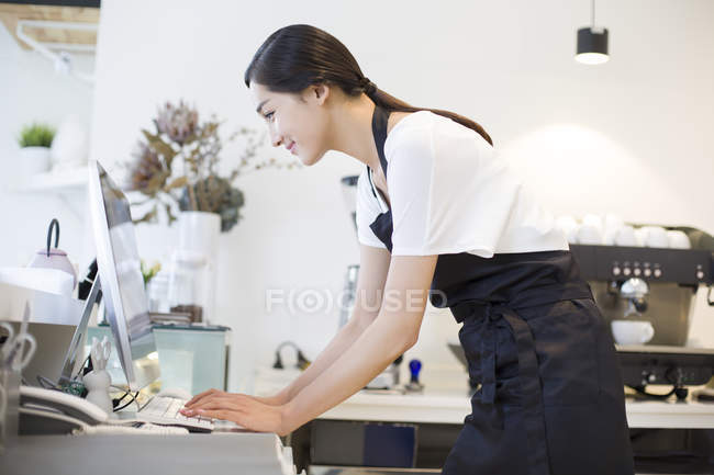 Chinese coffee shop owner using computer — Stock Photo