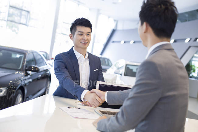 Chinese man shaking hands with car dealer in showroom — Stock Photo