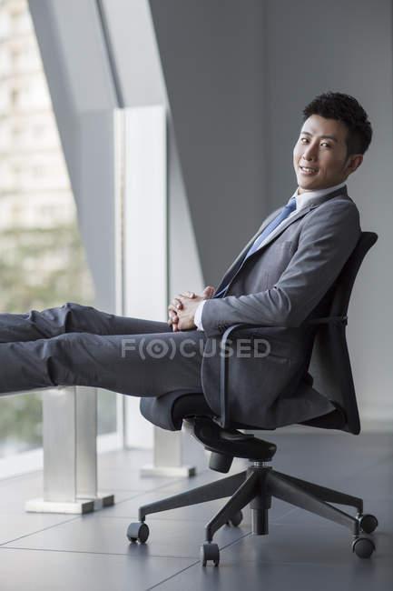 Китайский бизнесмен сидит в кресле и смотрит в камеру — стоковое фото