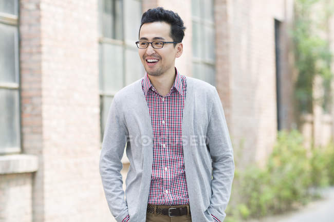 Mid adult chinese man standing on street and smiling — Stock Photo