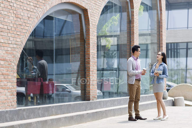 Chinese colleagues talking on street with coffee and digital tablet — Stock Photo