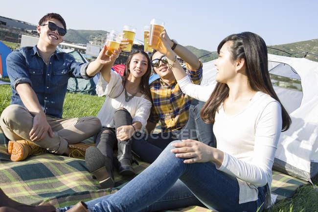 Amigos chineses sentado na manta com cerveja no camping — Fotografia de Stock