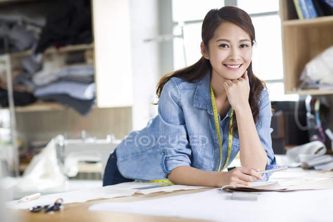 Китайська моди дизайнер спершись на стіл в студії і посміхається — стокове фото