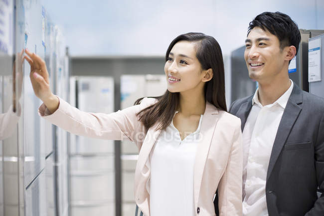 Chinese couple choosing refrigerator in electronics store — Stock Photo