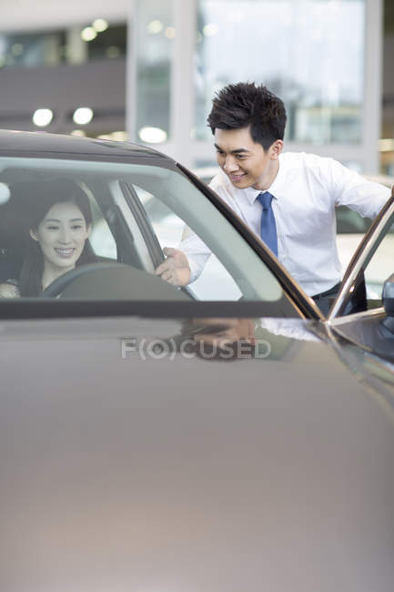Chinese woman taking test drive with car dealer assistance — Stock Photo