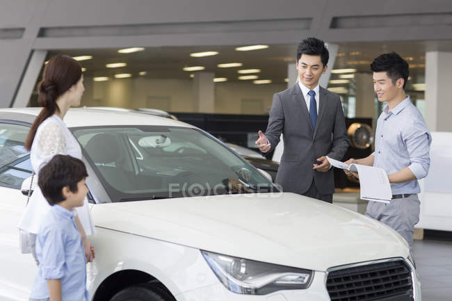 Chinese car seller helping family choosing car in showroom — Stock Photo