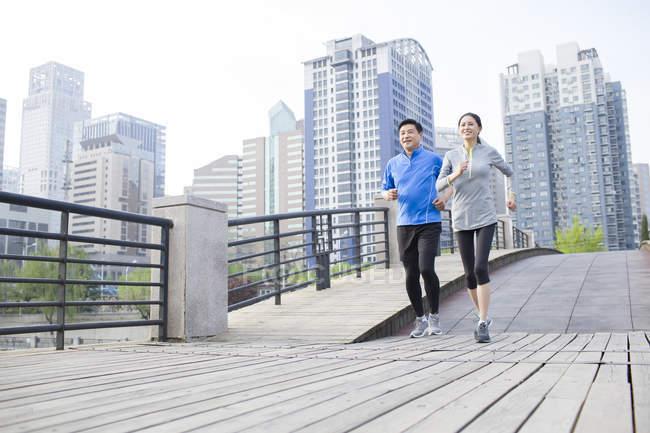 China pareja madura corriendo en puente de la ciudad - foto de stock
