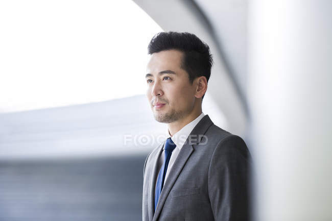 Serious chinese businessman looking away — Stock Photo