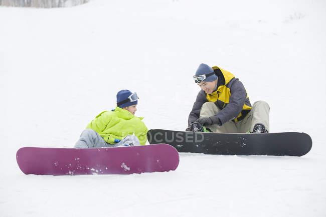 Китайський батька, допомагаючи син носіння сноубординг передач на снігу — стокове фото