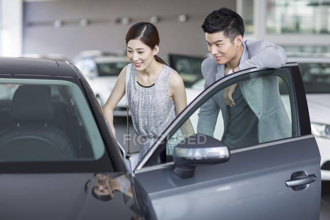 Китайська пара, дивлячись на автомобіль в автосалоні — стокове фото