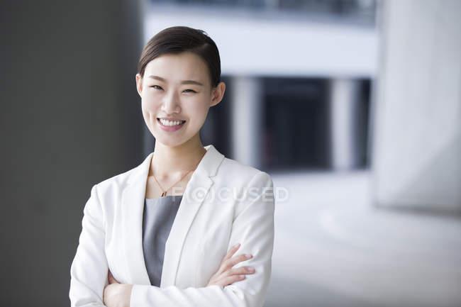 Empresária chinesa de pé com os braços dobrados — Fotografia de Stock