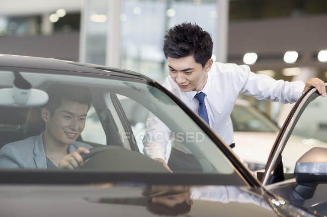 Chinese man taking test drive with car dealer assistance — Stock Photo