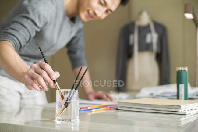 Chinese fashion designer painting sketch at desk — Stock Photo