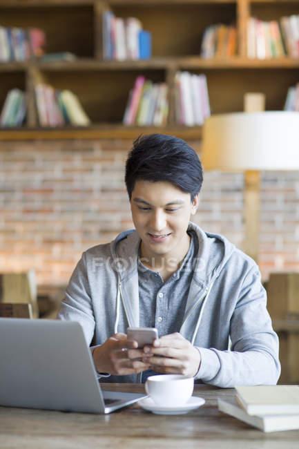 Uomo cinese utilizzando smartphone nella caffetteria — Foto stock