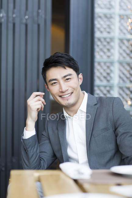 Chinese man sitting in restaurant and looking in camera — Stock Photo