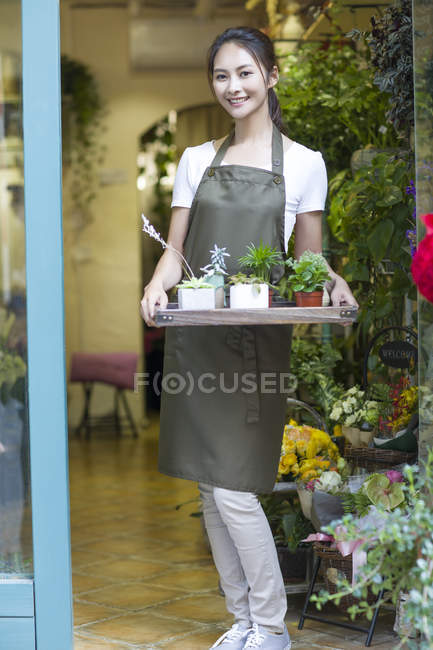 Female chinese florist holding tray with plants in store doorway — Stock Photo