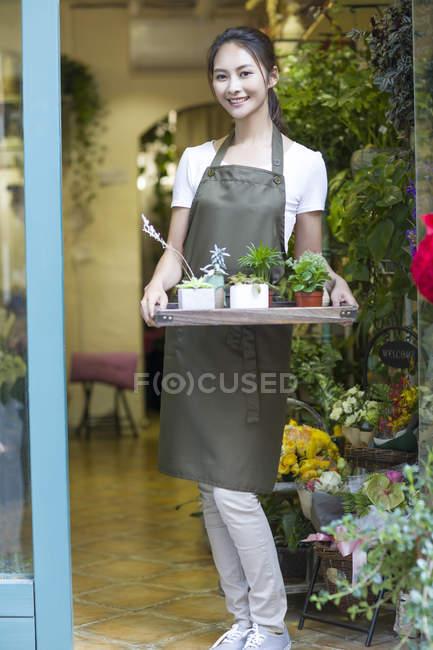 Самка китайского флориста держит траву с растениями в дверях магазина — стоковое фото
