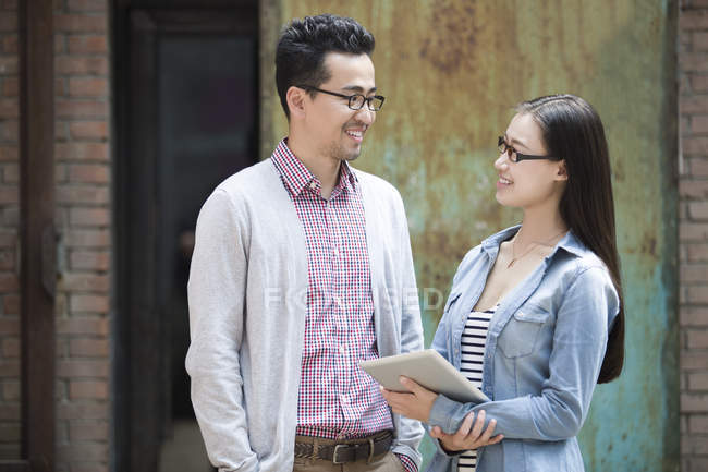 Chinese colleagues talking on street with digital tablet — Stock Photo