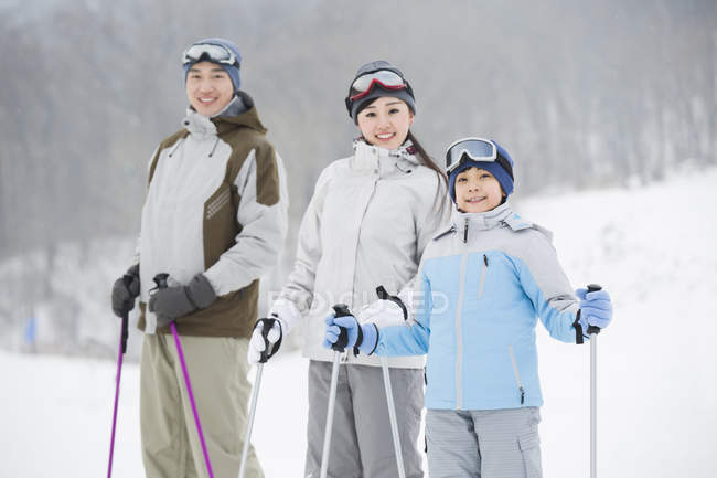 Chinese parents with son posing on snowy slope — Stock Photo