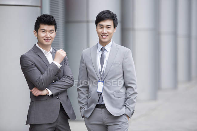 Uomini d'affari cinesi in piedi sulla strada e guardando in macchina fotografica — Foto stock