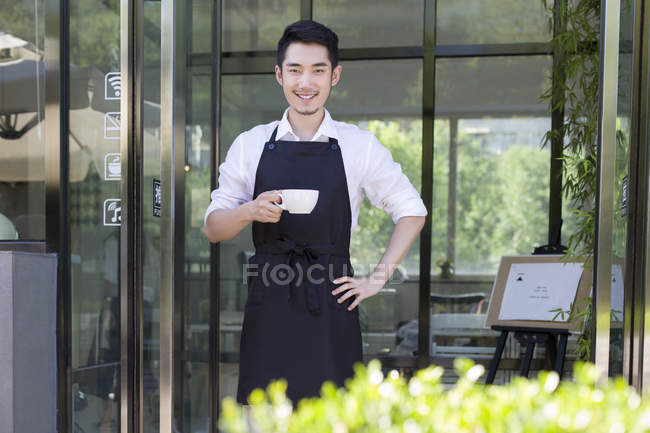 Shopkeeper standing in doorway of cafe with cup of coffee — Stock Photo