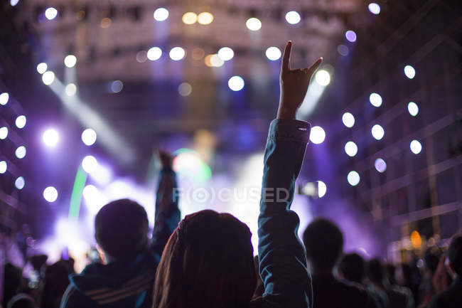 Woman making rock and roll sign at concert — Stock Photo