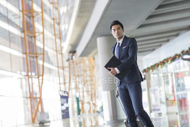 Uomo d'affari cinese che cammina in aeroporto con valigia e laptop — Foto stock