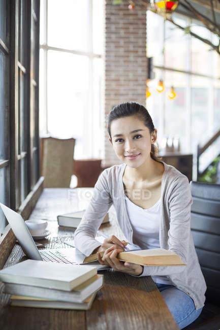 Femme chinoise assise dans un café et tenant un livre — Photo de stock