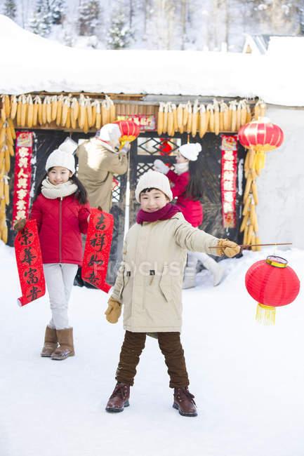 Enfants chinois aidant parents porte avec lanternes de décoration — Photo de stock