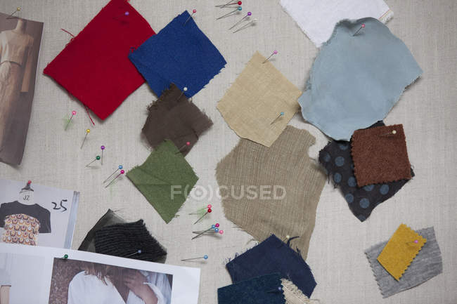 Different fabric swatches on pin board — Stock Photo