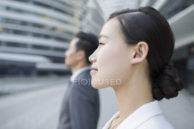Chinese businesswoman and businessman looking at view, side view — Stock Photo