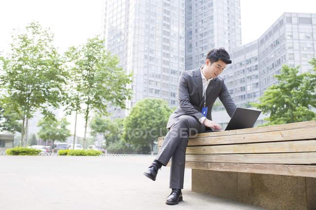 Homme d'affaires chinois travaillant avec un ordinateur portable sur banc de rue — Photo de stock