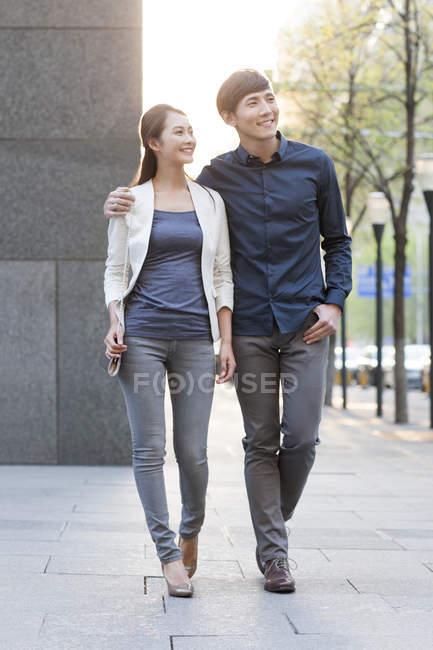 Cinese coppia a piedi sul marciapiede in città e guardando altrove — Foto stock