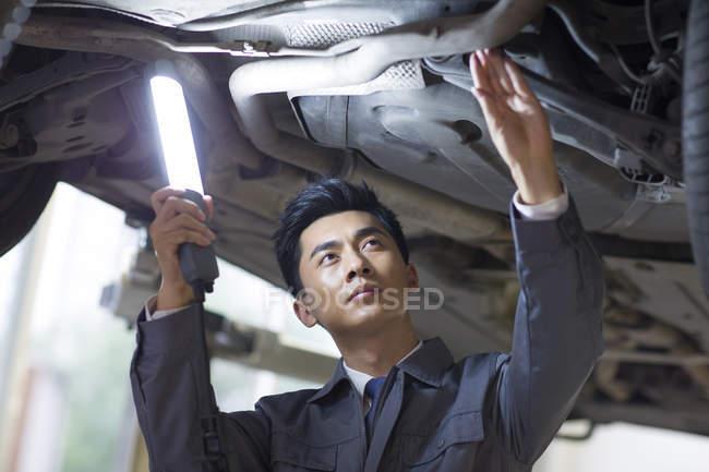 Chinese auto mechanic examining car with flashlight — Stock Photo