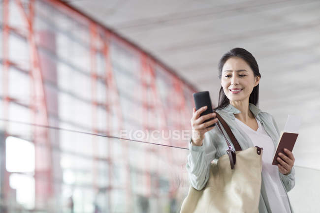 Mujer china sosteniendo teléfono inteligente y billete en el aeropuerto - foto de stock