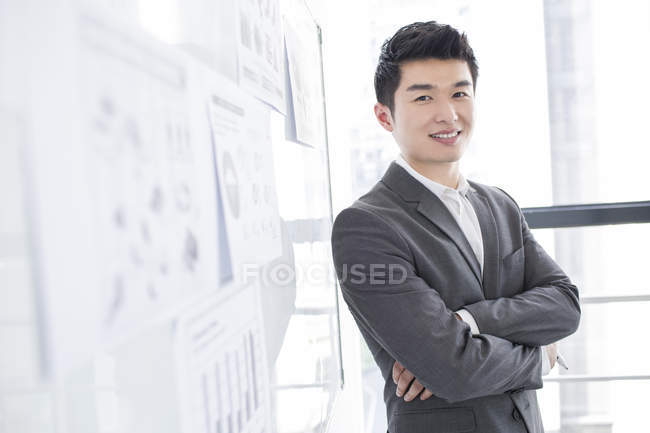 Chinese businessman standing with arms folded at whiteboard — Stock Photo