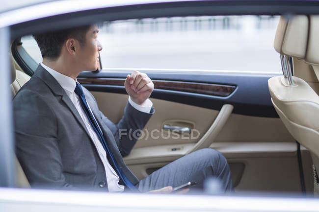 Chinese businessman sitting on car back seat — Stock Photo
