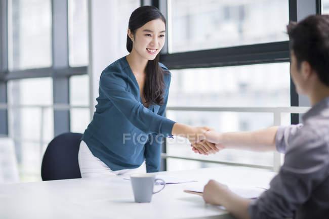 Китаянка пожимая руки на заседании — стоковое фото