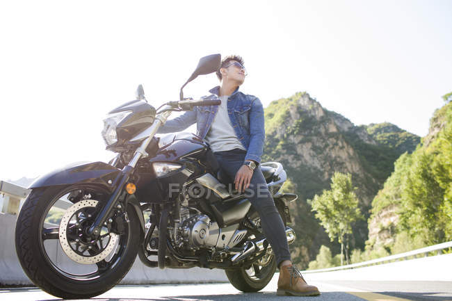 Chinese man sitting on motorcycle on highway — Stock Photo