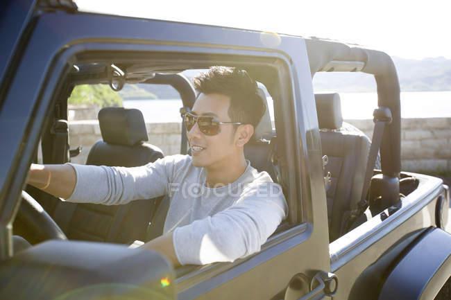 Китаєць водіння автомобіля і посміхається — стокове фото