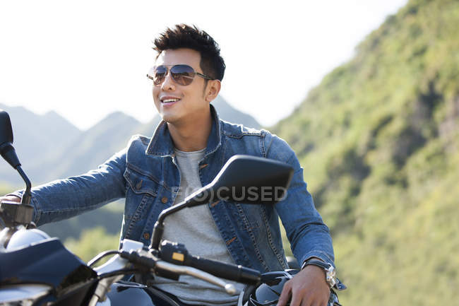 Китайський людини, що сидить на мотоциклі на шосе — стокове фото