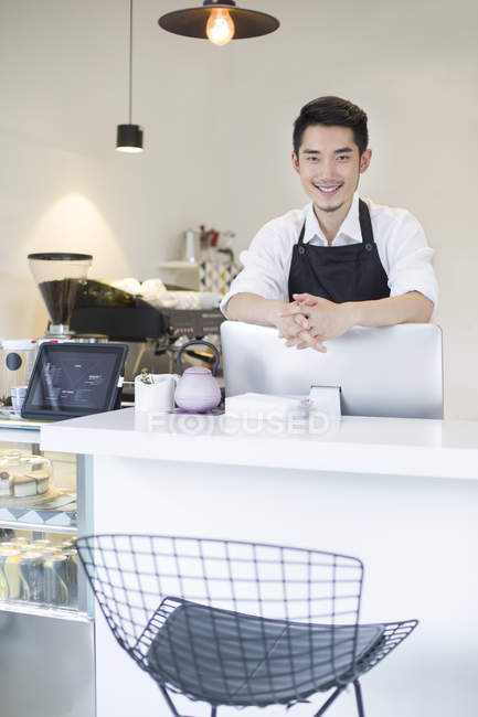 Chinese coffee shop owner at counter — Stock Photo