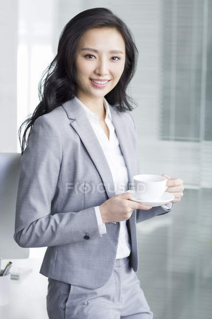 Chinesische Geschäftsfrau macht Kaffeepause bei der Arbeit — Stockfoto