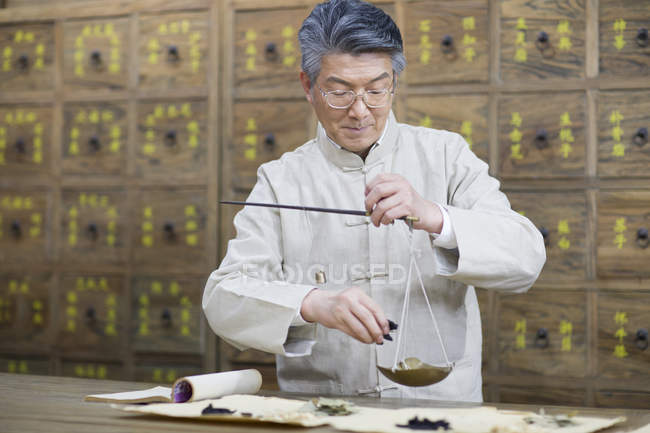 Chinese pharmacist working with weight scale in pharmacy — Stock Photo