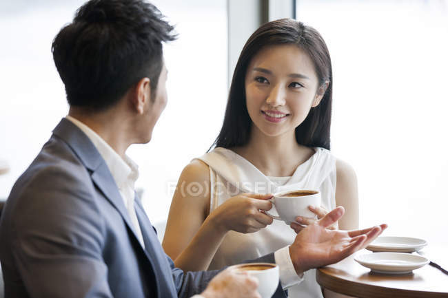 Chinese man and woman talking with coffee in cafe — Stock Photo