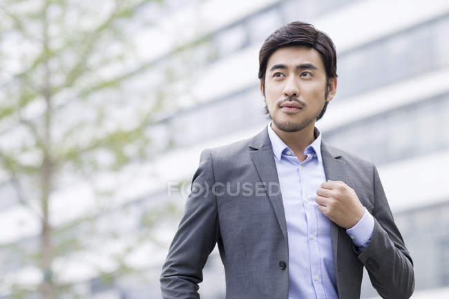 Chinese businessman standing on street and looking away — Stock Photo