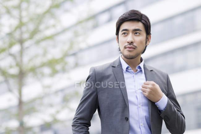 Китайський бізнесмен, стоячи на вулиці і дивитися вбік — стокове фото