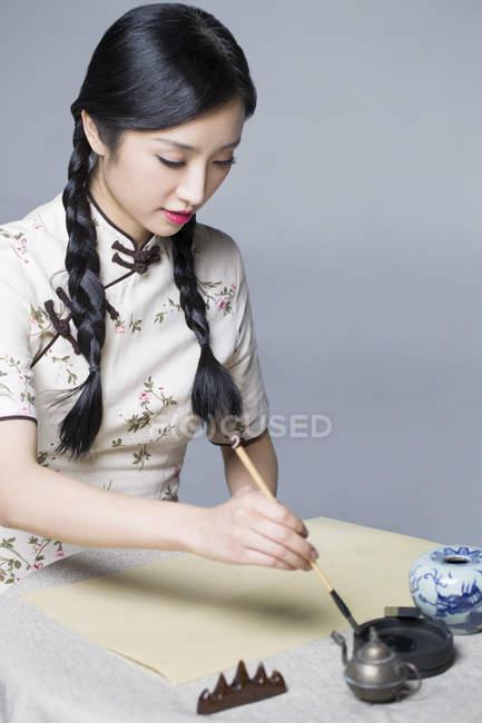 Femme chinoise en habit traditionnel pratiquant la calligraphie — Photo de stock