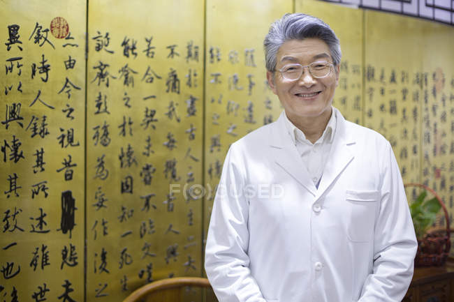 Senior chinese doctor standing in clinic and looking in camera — Stock Photo