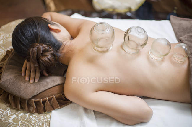 Woman lying down with vacuum cupping glass cups — Stock Photo